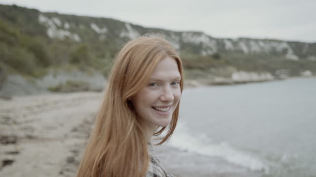 portrait of beautiful serene redhead woman dancing on beach smiling and looking at camera - nature stock videos & royalty-free footage