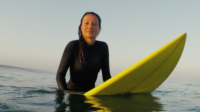 Portrait of beautiful, smiling female surfer sitting on surfboard at sunrise in surf break and waves at deserted sandy beach at Atlantic ocean coast in the south of France.