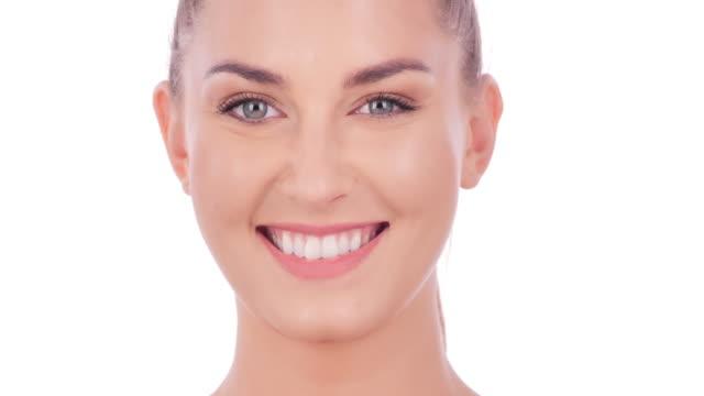 porträt der schönen lächelnden frau auf weißem hintergrund. ausdrucksstarke gesichtsausdrücke. kosmetologie und spa - reinheit stock-videos und b-roll-filmmaterial