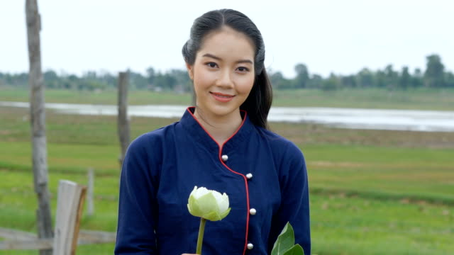 vídeos y material grabado en eventos de stock de retrato de la hermosa mujer tailandesa sosteniendo el loto y sonriendo en el puente de madera. - posa del loto