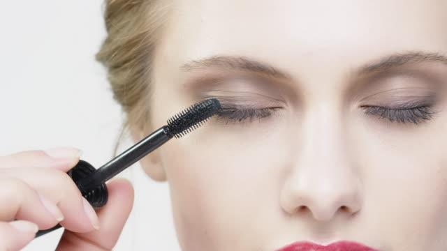 vídeos de stock, filmes e b-roll de retrato de mulher bonita aplicar rímel - pincel