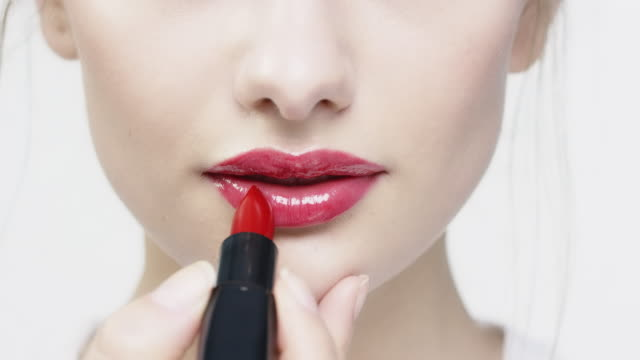 portrait of beautiful woman applying red lipstick - make up stock videos & royalty-free footage