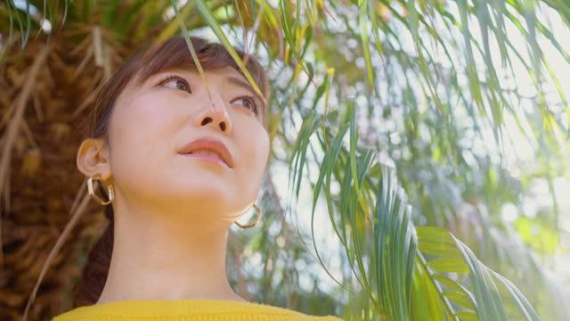 vídeos de stock, filmes e b-roll de retrato de mulher bonita em suéter amarelo na natureza - brinco