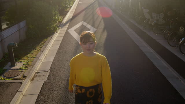 portrait of beautiful woman in yellow sweater walking in street - jumper stock videos & royalty-free footage