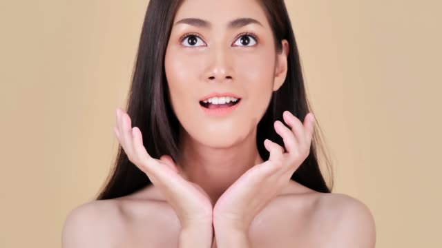 portrait of beautiful woman on brown background.beautiful woman touching her face.expressive facial expressions.cosmetology and spa - brown background stock videos and b-roll footage