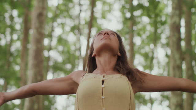 portrait of beautiful woman raising arms taking deep breath in forest - forza video stock e b–roll