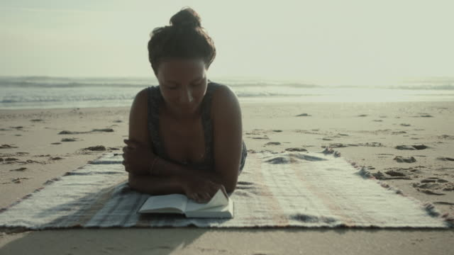 portrait of beautiful woman reading book on a blanket at the beach at the atlantic ocean in the south of france - piedi alzati video stock e b–roll