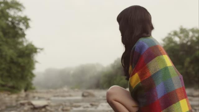 portrait of beautiful woman sitting on rock in nature - eingewickelt stock-videos und b-roll-filmmaterial