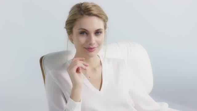 vídeos de stock e filmes b-roll de portrait of beautiful woman sitting on white chair - higiene