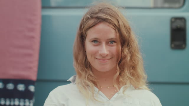 stockvideo's en b-roll-footage met portrait of beautiful woman smiling into camera - gekruld haar