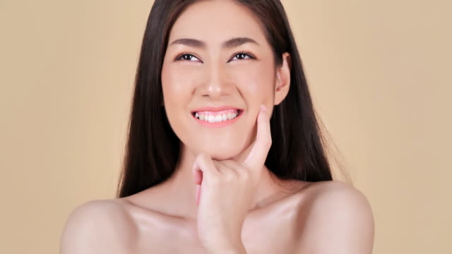 portrait of beautiful woman smiling on brown background.beautiful woman touching her face.expressive facial expressions.cosmetology and spa - brown background stock videos and b-roll footage