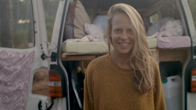 vidéos et rushes de portrait of beautiful woman standing in front of her bus in the forest in the south of france in the morning. - la vingtaine
