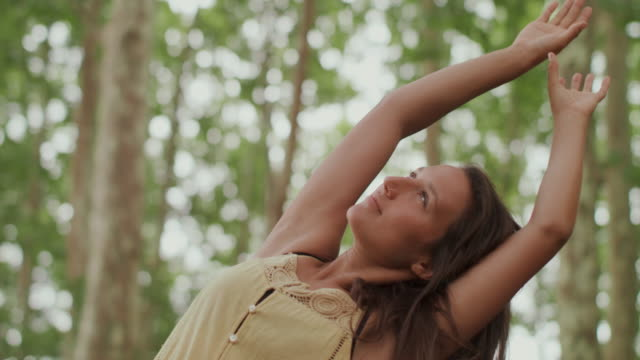 Portrait of beautiful woman stretching in the forest