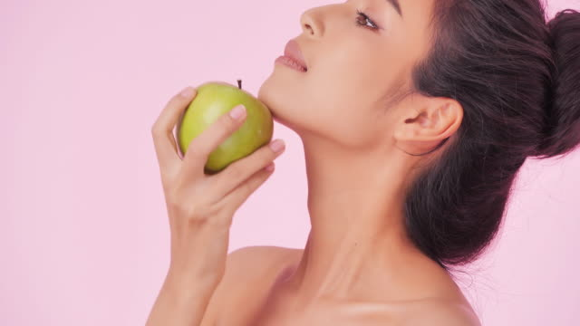 portrait of beautiful woman with apple on pink background.clean and balanced healthy food concept.healthy food,diet and fitness concept.organic food.health care and medicine concept.video: diverse portraits - young women stock videos & royalty-free footage