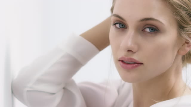 Porträtt av vacker kvinna med blå ögon av vägg
