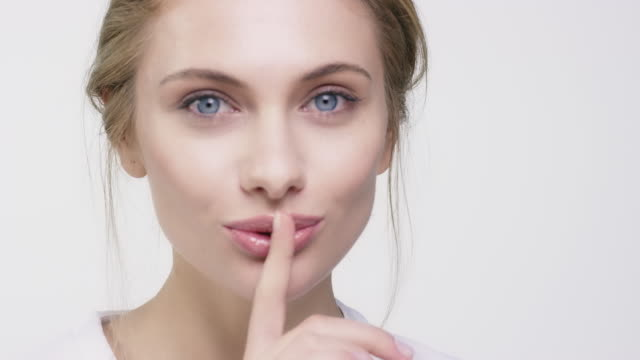 portrait of beautiful woman with finger on lips - beautiful woman stock videos & royalty-free footage