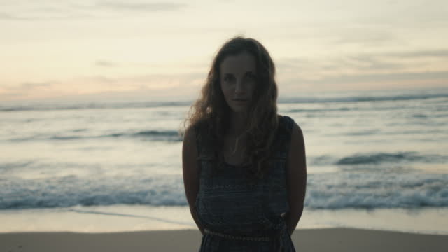 portrait of beautiful young woman at sunset on a deserted beach at atlantic ocean in the south of france - hands behind back stock videos and b-roll footage