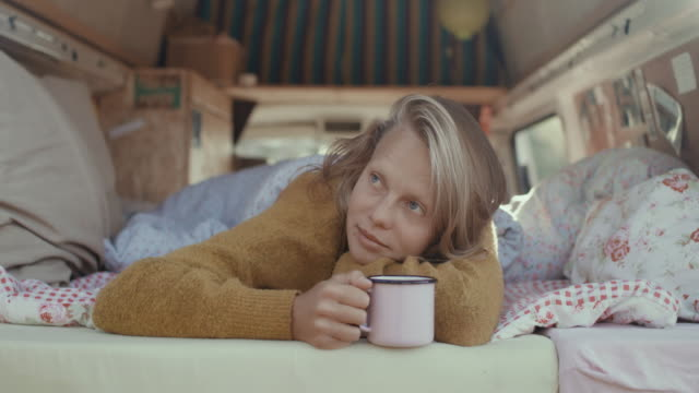 portrait of beautiful young woman drinking coffee in the back of her motor home in the morning. - persona attraente video stock e b–roll