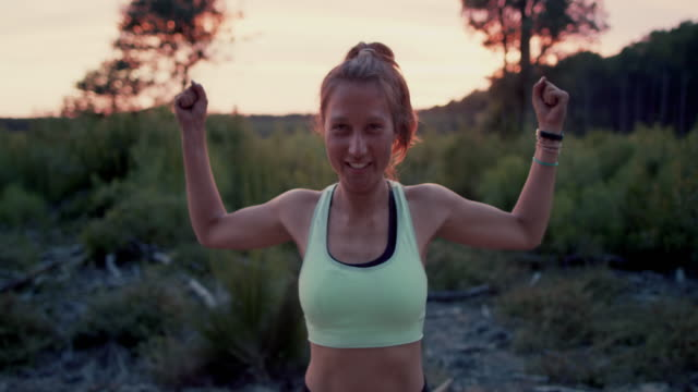 portrait of beautiful young woman flexing muscles, smiling, laughing with sand on her face and body after outdoors yoga practice at sunrise in the forest in the south of france. - flexing muscles stock videos and b-roll footage