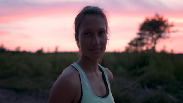 portrait of beautiful young woman looking into camera at sunrise in the forest in the south of france. - gente comune video stock e b–roll