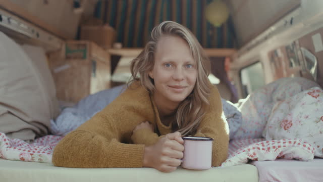 portrait of beautiful young woman looking into camera, drinking coffee in the back of her motor home in the morning. - gemütlich stock-videos und b-roll-filmmaterial