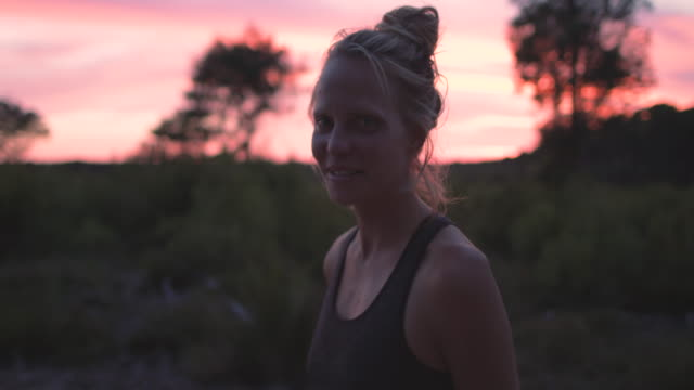 portrait of beautiful young woman looking into camera smiling at sunrise in the forest in the south of france. - capelli biondi video stock e b–roll