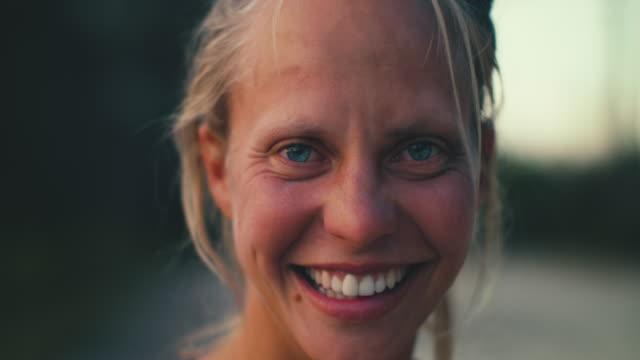 stockvideo's en b-roll-footage met portrait of beautiful young woman smiling into camera at sunrise in the south of france - glimlachen