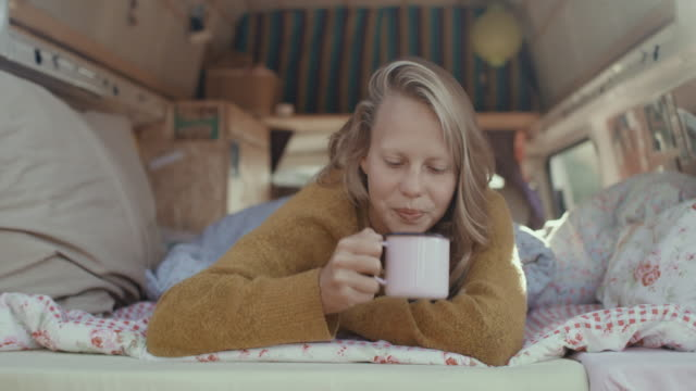 vídeos de stock e filmes b-roll de portrait of beautiful young woman smiling into camera, drinking coffee in the back of her motor home in the morning. - café bebida