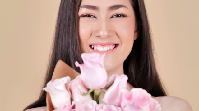 portrait of beautiful young woman with flowers on a brown background.brunette woman with luxury makeup.perfect skin.spa portrait of beautiful woman with clear healthy skin.expressive facial expressions.cosmetology and spa - brown background stock videos and b-roll footage