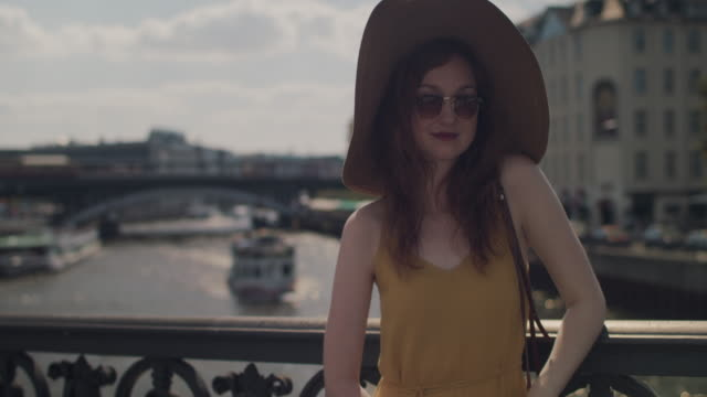 portrait of beautiful young woman with red hair and sun hat standing on bridge, looking into camera, looking over sunglasses in berlin, germany on a sunny day. - part of a series stock videos & royalty-free footage