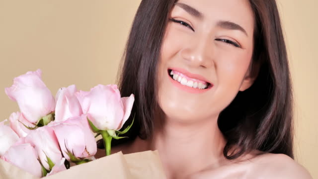 portrait of beautiful young woman with rose flowers on a brown background.brunette woman with luxury makeup.perfect skin.spa portrait of beautiful woman with clear healthy skin.expressive facial expressions.cosmetology and spa - body care and beauty stock videos & royalty-free footage