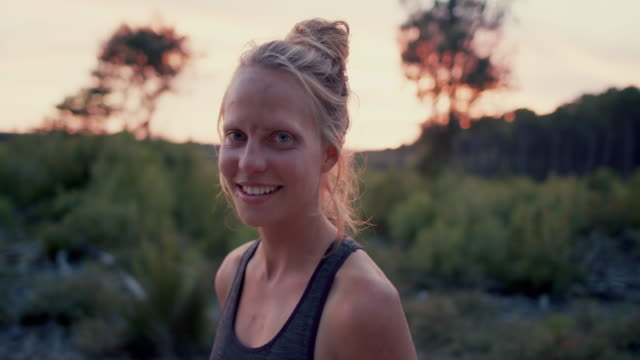 portrait of beautiful young woman with sand in her face after outdoors yoga practice smiling, looking into camera flexing muscles at sunrise in the forest in the south of france. - flexing muscles stock videos and b-roll footage
