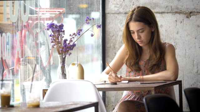 portrait of beautiful young woman with with pen writing on notebook at coffee shop - pen stock videos and b-roll footage