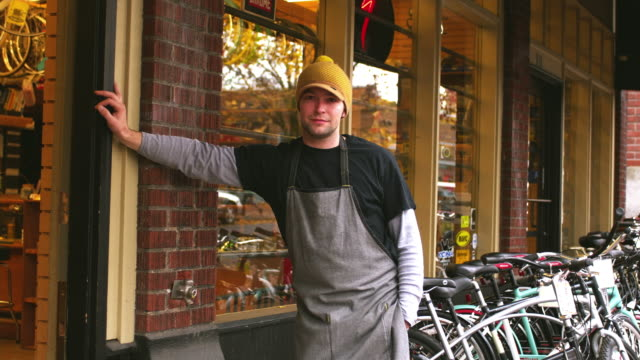 ms portrait of bike shop owner in front of shop / portland, oregon, usa - portland oregon bike stock videos & royalty-free footage