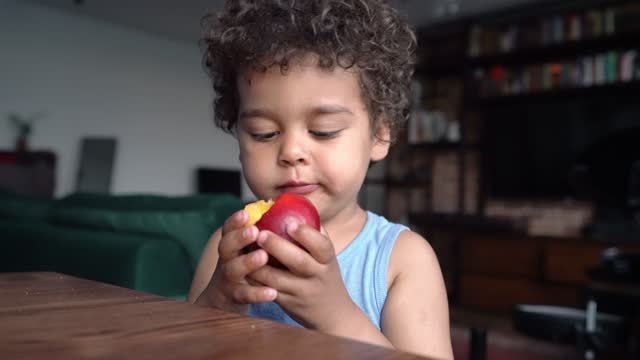 portrait of black boy 3 years old eating peach - childhood stock videos & royalty-free footage