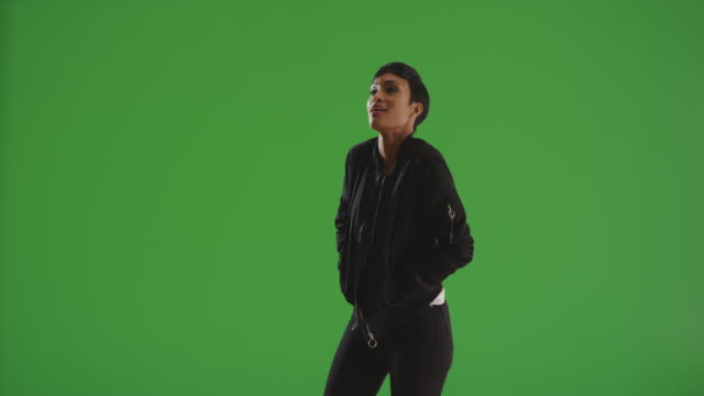 vídeos de stock, filmes e b-roll de portrait of black female dancing casually on green screen - multi coloured