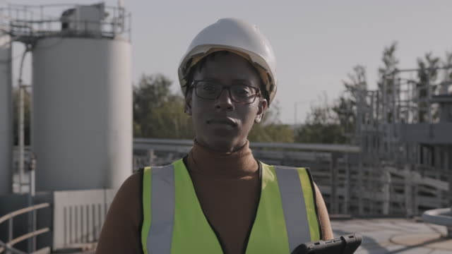 portrait of black female industrial worker looking at camera wearing high vis vest and hard hat helmet at chemical plant - manufacturing occupation stock videos & royalty-free footage
