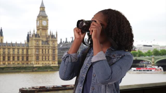 vídeos de stock, filmes e b-roll de portrait of black female standing by river thames in london, taking pictures - jaqueta jeans