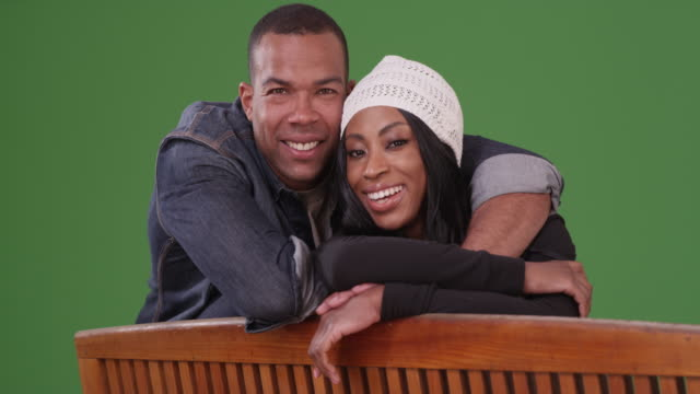 portrait of black man and woman looking over back of bench on green screen - panchina video stock e b–roll