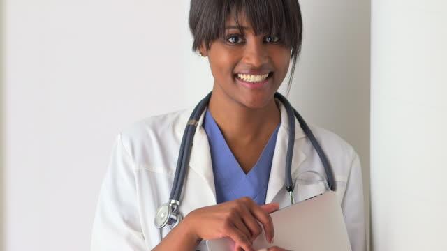 vidéos et rushes de portrait of black woman doctor smiling - masque de chirurgien