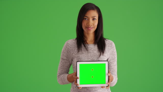 portrait of black woman holding tablet with green screen for custom content - 電子手帳点の映像素材/bロール