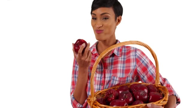 portrait of black woman taking bite of delicious red apple and smiling in studio - red delicious stock videos & royalty-free footage