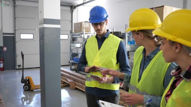 vídeos de stock, filmes e b-roll de retrato de trabalhadores do colar azul no armazém. duas mulheres e um homem no workwear protetor. - operário de linha de produção
