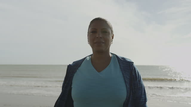 portrait of body positive mature black female model outdoors on beach, plus size obese overweight afro american woman looking at camera at sunrise - plus size model stock videos & royalty-free footage
