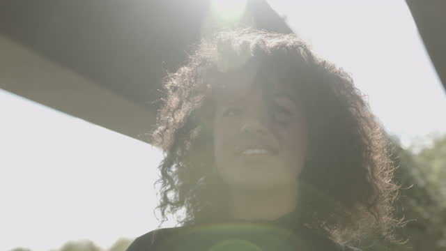 portrait of body positive young black female looking at camera under bridge with sun - body positivity stock-videos und b-roll-filmmaterial