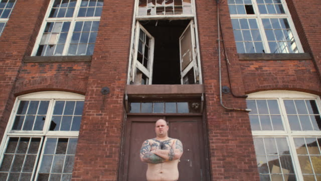 ms la portrait of bodybuilder in front of deserted factory, middletown, connecticut, usa - completely bald stock videos and b-roll footage