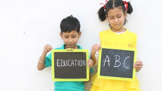 少年と少女のスレートを保持の肖像画 - 製図板点の映像素材/bロール