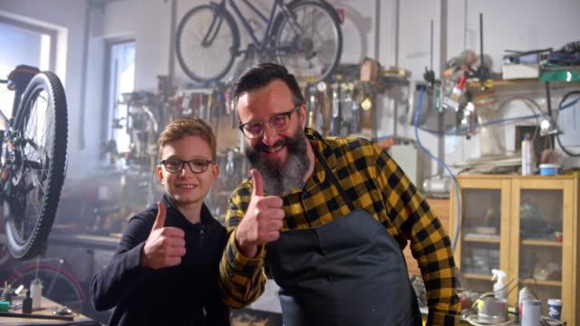 vídeos de stock e filmes b-roll de slo mo portrait of boy and his dad doing a thumbs up in their home workshop - família com um filho