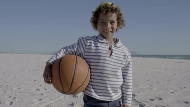 portrait of boy holding basketball at beach - basketball spielball stock-videos und b-roll-filmmaterial