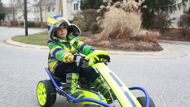 Portrait of boy in gocart backs up then goes forward on his way down a residential road.